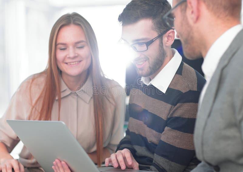Tre impiegati felici che lavorano alla linea con una compressa fotografie stock