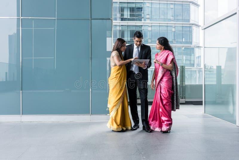 Tre indiska affärspersoner som inomhus använder en minnestavlaPC royaltyfri bild