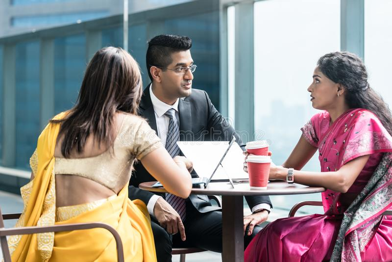 Tre indiska affärspersoner som talar under avbrott på arbete arkivbild