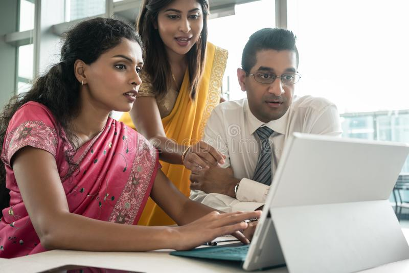 Tre indiska anställda som tillsammans arbetar runt om en bärbar dator royaltyfri bild
