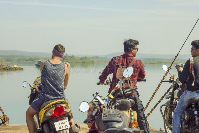 Tre indiska grabbar på motorcyklar på färjan mot bakgrunden av floden och gräsplanen arkivfoto