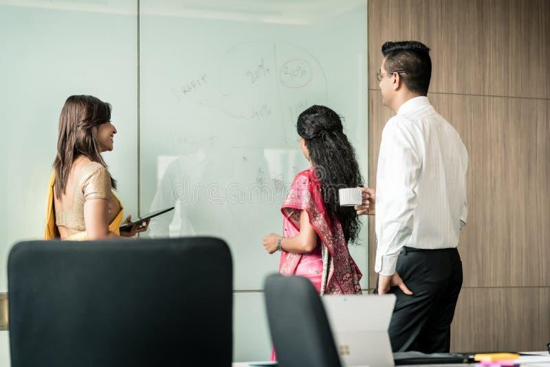 Tre indiska kollegor som skriver idéer under idékläckning arkivfoto