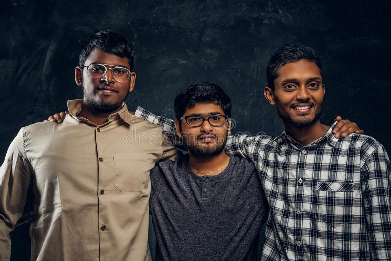 Tre indiska studentvänner står i en kram och en blick in i kameran i studio royaltyfria bilder