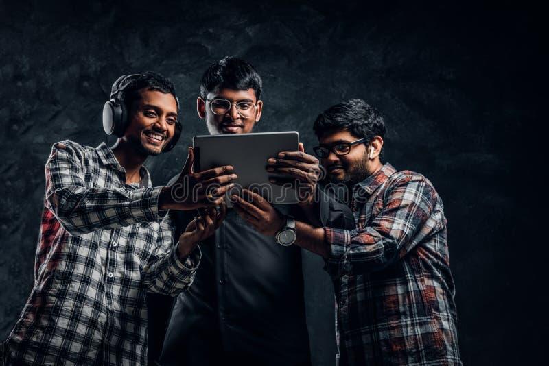 Tre indiska vänner som håller ögonen på något som är rolig i ett minnestavlaanseende i en mörk studio royaltyfria foton