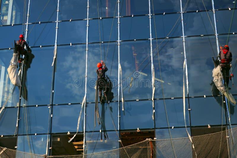 Tre industriella klättrare på en exponeringsglasfasad royaltyfri fotografi