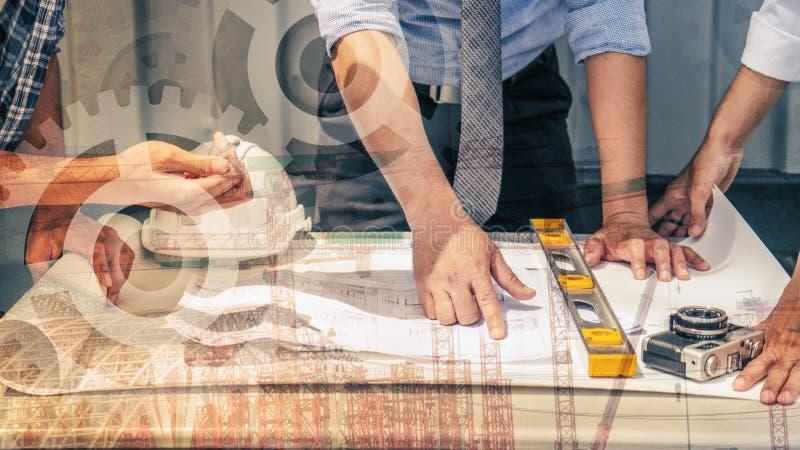 Tre ingegneri che lavorano con il modello del cantiere sulla tavola fotografia stock