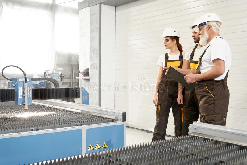 Tre ingegneri che stanno vicino al CNC sulla fabbrica del metallo immagini stock libere da diritti