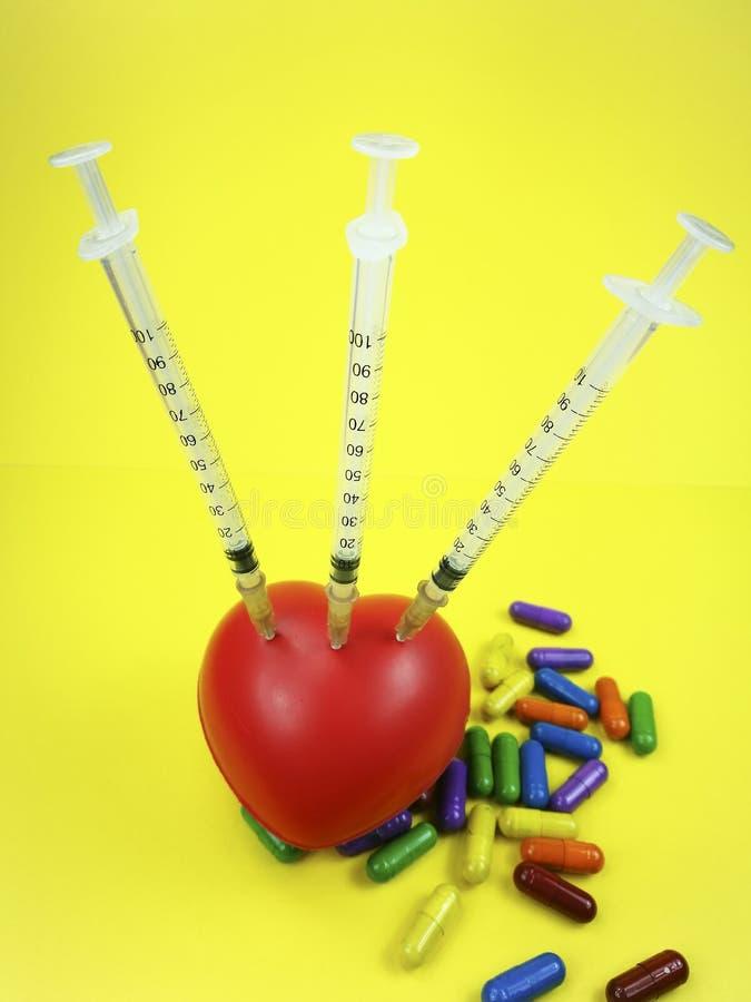 Tre injektionssprutor sörjde till en röd svampig hjärta med preventivpillerar royaltyfria bilder