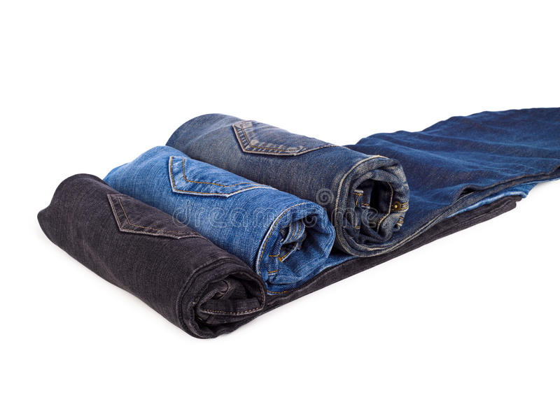 Tre jeans rotolati del denim su bianco immagine stock