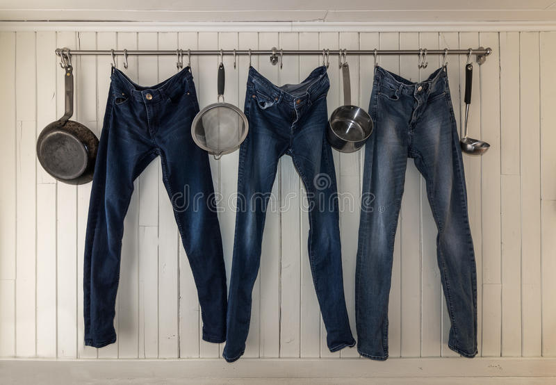 Tre jeans som hänger på en kökstång för att torka royaltyfri bild