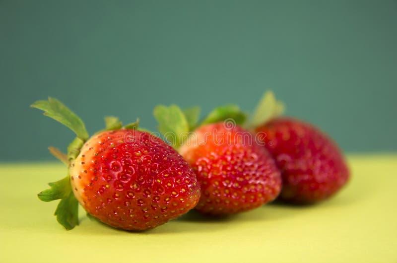 Tre jordgubbar i grön bakgrund royaltyfri fotografi