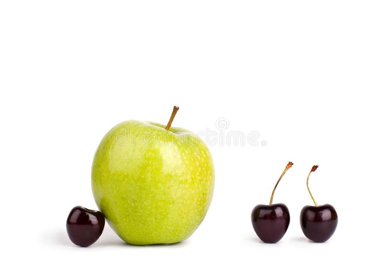 Tre körsbärsröda bär och ett stort grönt äpple på vit bakgrund isolerat slut upp makro royaltyfria foton