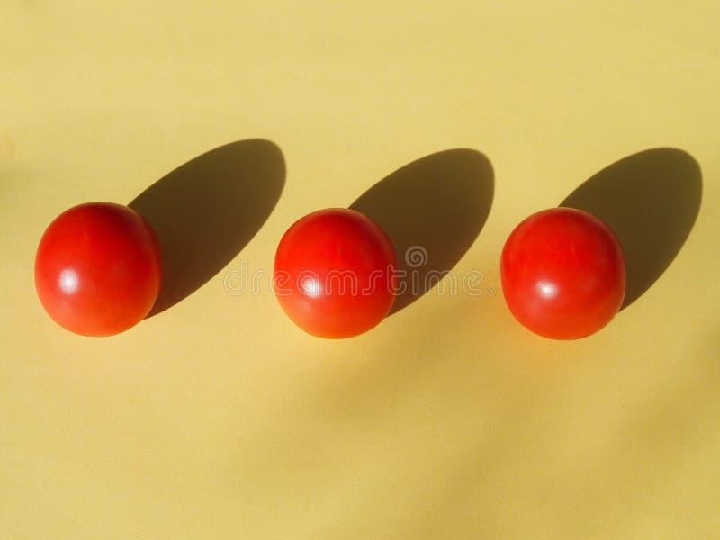Tre körsbärsröda tomater ligger sjukvårdaren på en gul bakgrund royaltyfria bilder