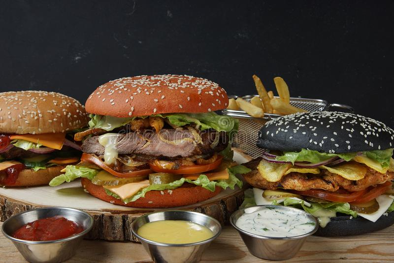 Tre kalla hamburgare och olika såser till franska småfiskar arkivfoto