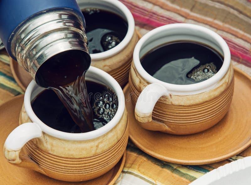 Tre keramiska koppar och termos med kaffe royaltyfri bild