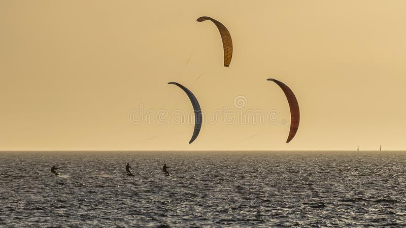 Tre kitesurfers al tramonto davanti alla spiaggia di Fremantle, Australia occidentale fotografie stock
