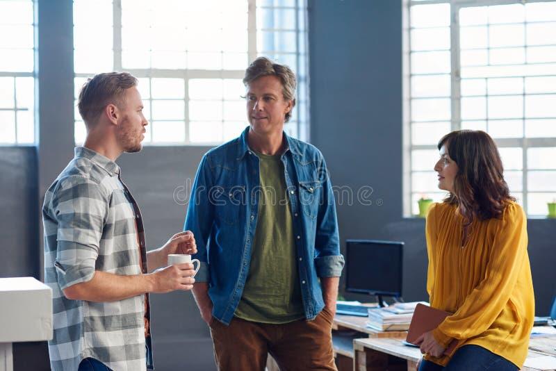 Tre kollegor som står i ett modernt kontor som tillsammans talar arkivfoto