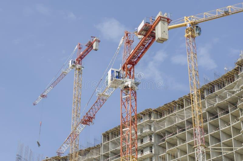 Tre konstruktionskranar på bakgrunden av ett monolitiskt hus under konstruktion arkivfoton