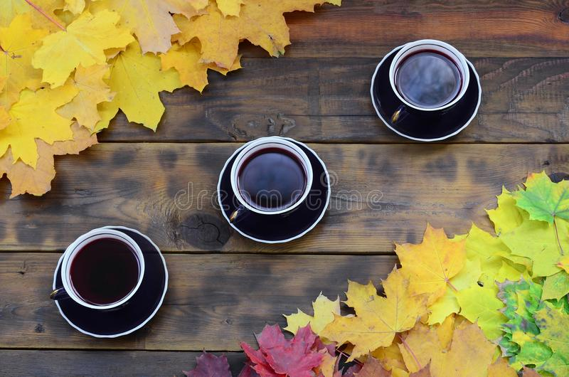 Tre kopp te bland en uppsättning av att gulna stupade höstsidor på en bakgrundsyttersida av naturliga träbräden av mörk brunt royaltyfri fotografi