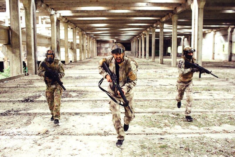 Tre krigare med utrustning kör ner stort och ljust rum Två av dem ser till sidorna medan mannen in arkivbild