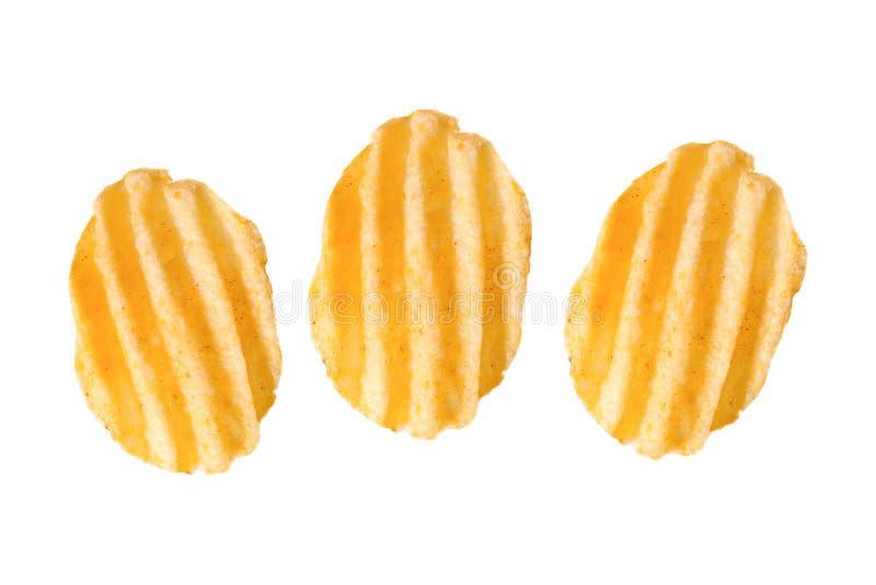 Tre krusiga potatischiper på vit arkivbild