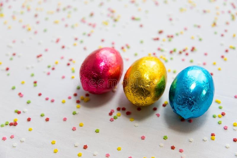 Tre kul?ra chokladeaster ?gg p? vit bakgrund och f?rgrika konfettier arkivbild