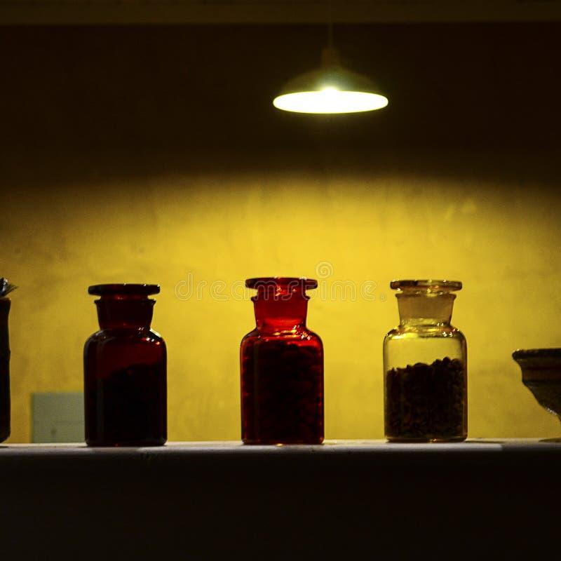 Tre kulöra flaskor i en linje under ett hängande ljus arkivbilder