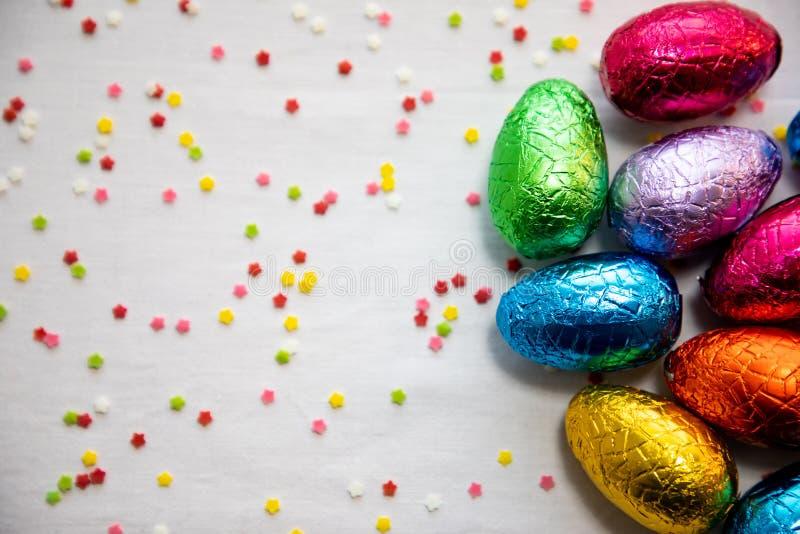 Tre kul?ra chokladeaster ?gg p? vit bakgrund och f?rgrika konfettier royaltyfri fotografi