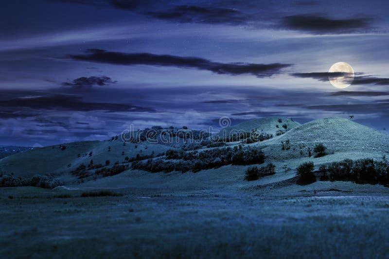 Tre kullar i sommarlandskap på natten royaltyfria bilder