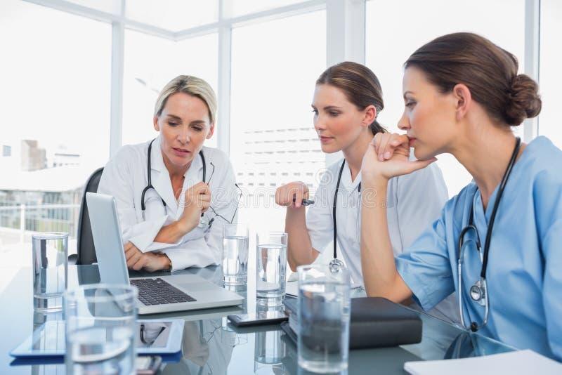 Tre kvinnadoktorer som håller ögonen på en bärbar dator royaltyfri foto