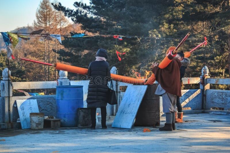 Tre kvinnaförsamlingsboer ställde in brand till de enorma pinnarna eller stearinljusen för jossaromrökelse i denYang templet i de arkivbilder