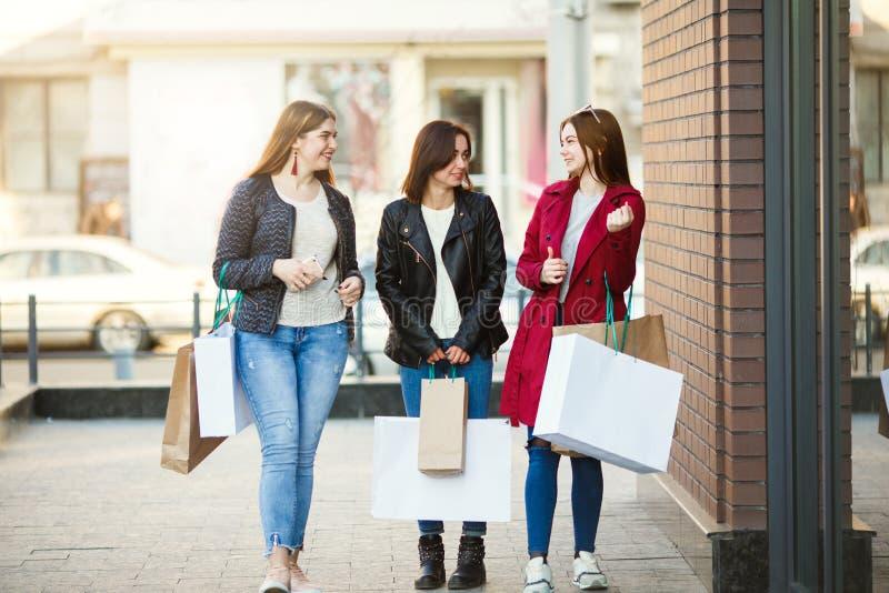 Tre kvinnavänner tycker om att shoppa tillsammans arkivfoto