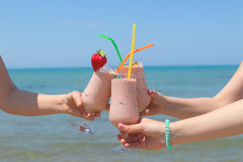 Tre kvinnliga händer rymmer jordgubbemilkshakar på bakgrunden av havet royaltyfri fotografi