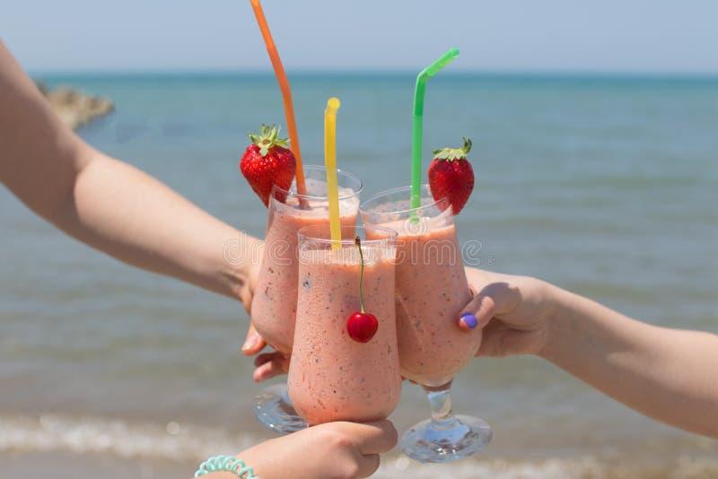 Tre kvinnliga händer rymmer jordgubbemilkshakar på bakgrunden av havet royaltyfria bilder