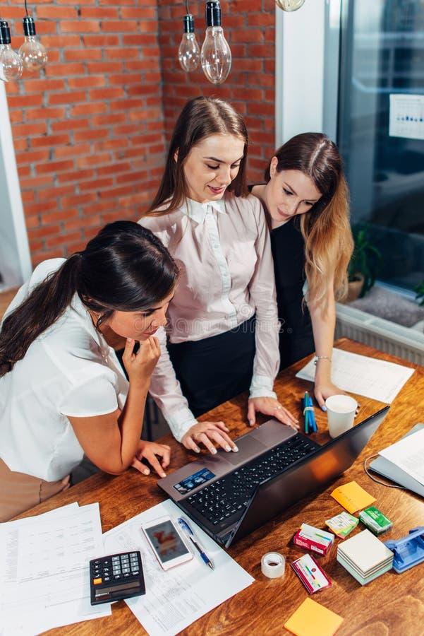 Tre kvinnliga högskolestudenter som arbetar på uppgiften som använder tillsammans bärbara datorn som hemma står royaltyfri fotografi