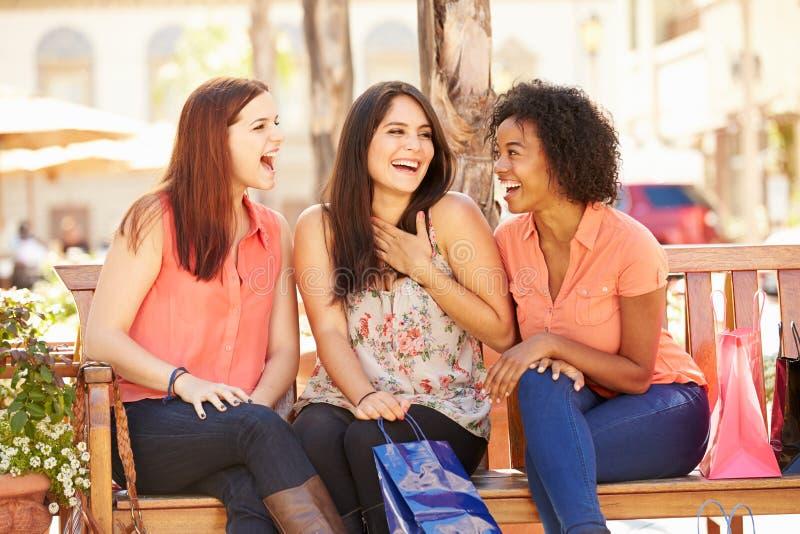 Tre kvinnliga vänner med shoppingpåsar som sitter i galleria arkivfoto