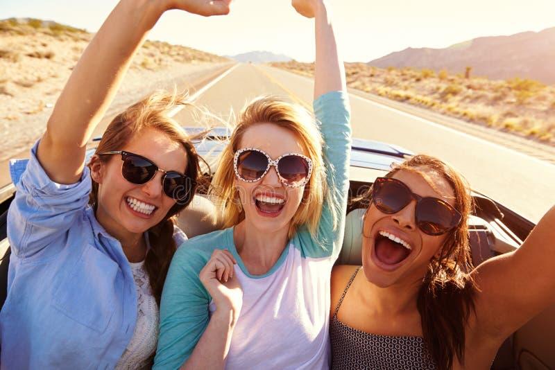 Tre kvinnliga vänner på vägtur i baksida av den konvertibla bilen arkivfoton