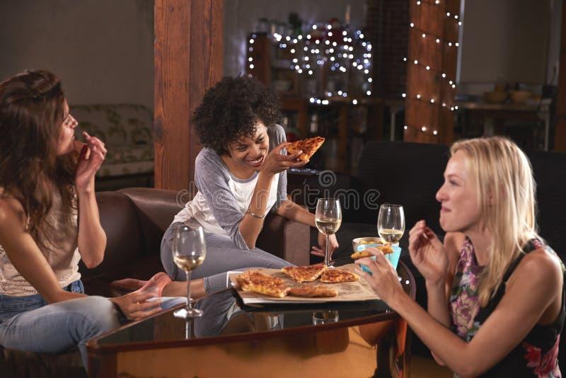Tre kvinnliga vänner som hänger ut hemma att äta pizza royaltyfria bilder