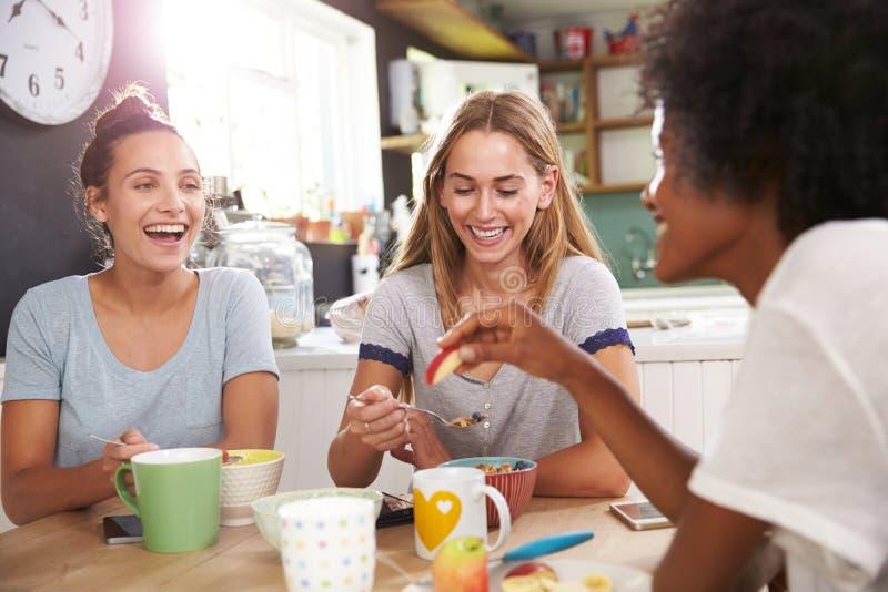 Tre kvinnliga vänner som hemma tycker om frukosten tillsammans fotografering för bildbyråer