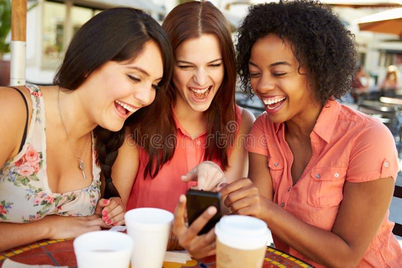 Tre kvinnliga vänner som läser textmeddelandet i CafÅ ½ fotografering för bildbyråer
