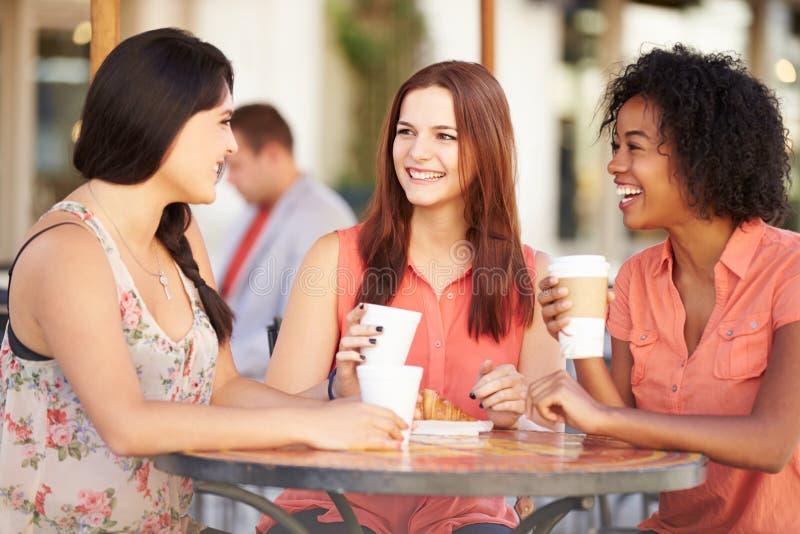 Tre kvinnliga vänner som möter i CafÅ ½ arkivfoton