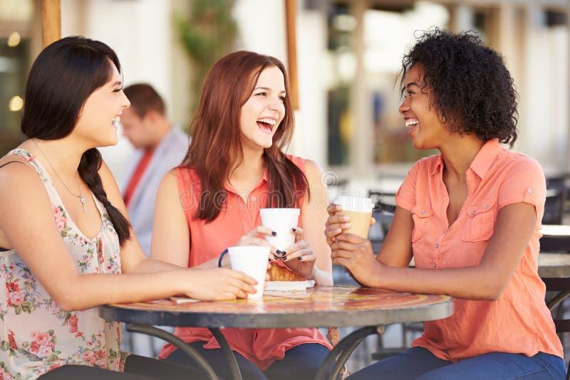 Tre kvinnliga vänner som möter i CafÅ ½ arkivbilder