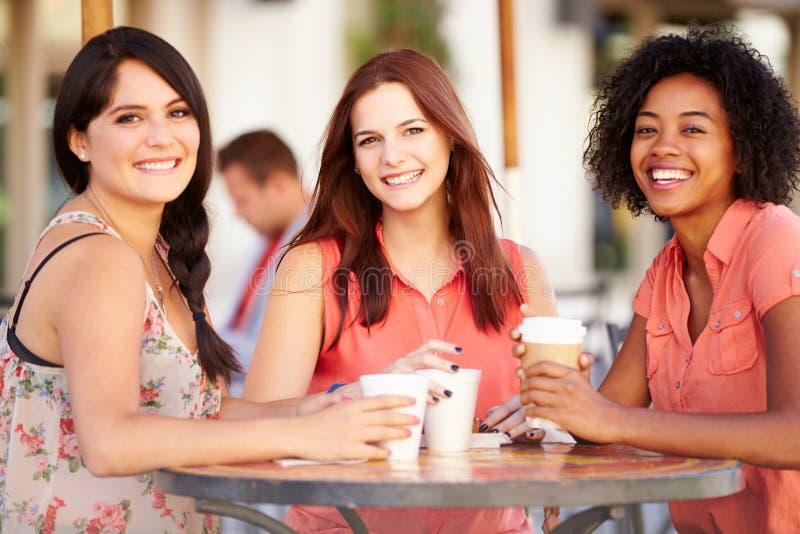 Tre kvinnliga vänner som möter i CafÅ ½ royaltyfria bilder