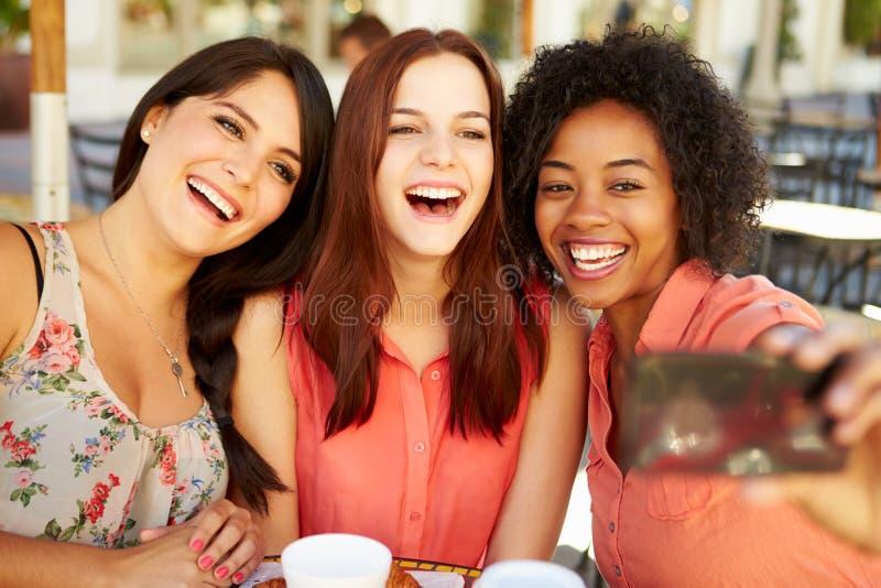 Tre kvinnliga vänner som tar Selfie i CafÅ ½ royaltyfri foto