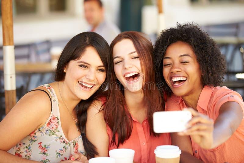 Tre kvinnliga vänner som tar Selfie i CafÅ ½ royaltyfri fotografi