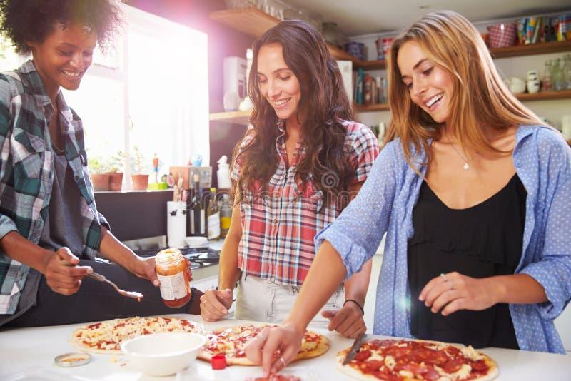 Tre kvinnliga vänner som tillsammans gör pizza i kök royaltyfri bild