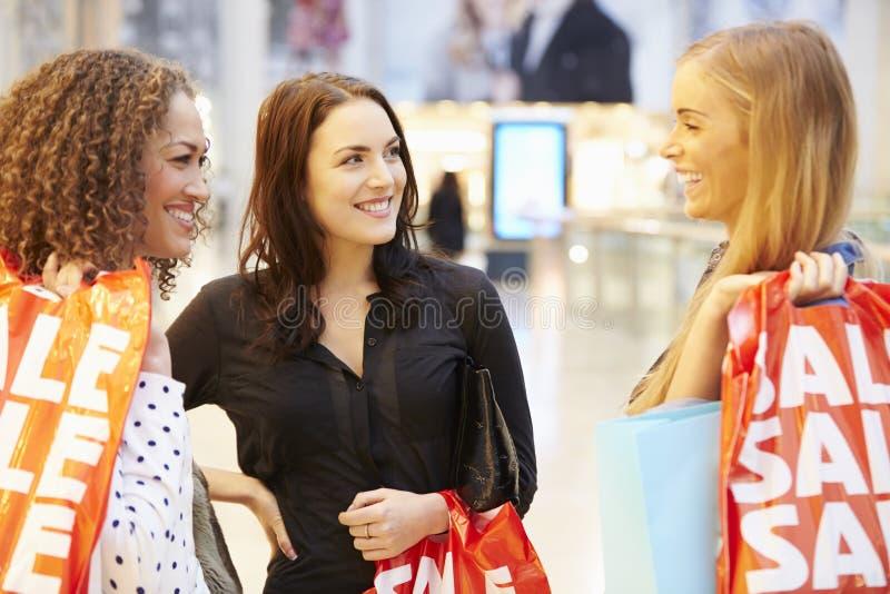 Tre kvinnliga vänner som tillsammans shoppar i galleria arkivbild