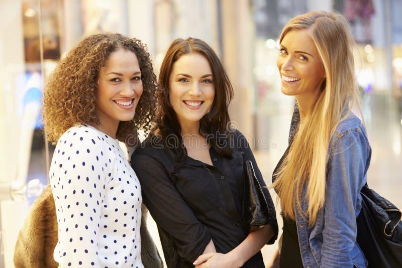 Tre kvinnliga vänner som tillsammans shoppar i galleria arkivfoto