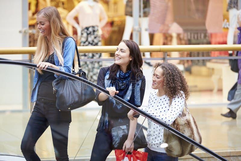 Tre kvinnliga vänner som tillsammans shoppar i galleria royaltyfria bilder