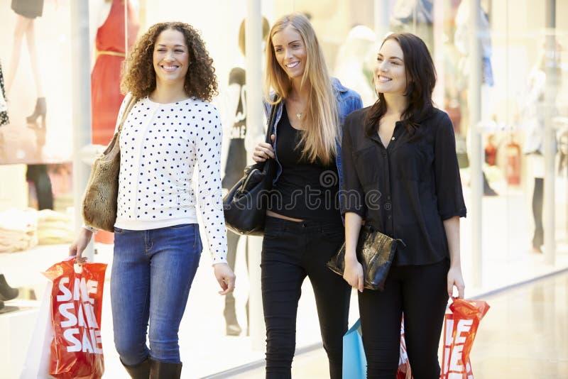 Tre kvinnliga vänner som tillsammans shoppar i galleria royaltyfri foto